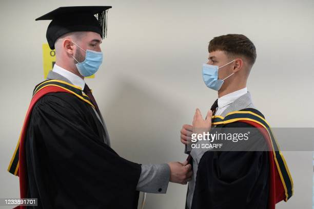 Graduates adjust each other's robes on campus at the University of Bolton before receiving their degree certificates in a Covid-safe, in-person...