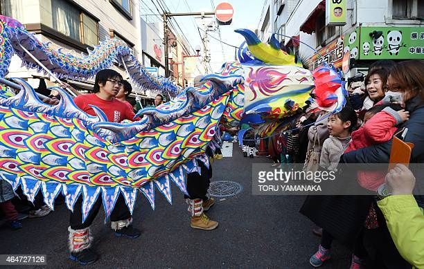 Graduates and students perform a dragon dance along a street during Lunar New Year celebrations in Yokohama's China Town on February 28 2015 Millions...