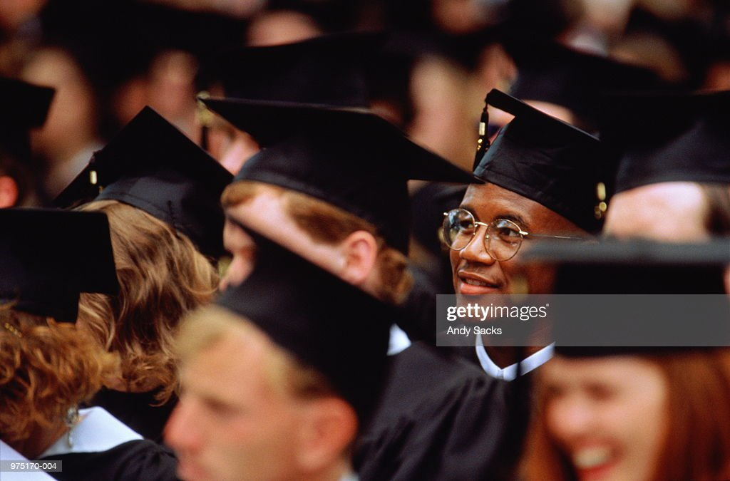 Graduates at graduation ceremony (focus on young man in glasses) : Stock Photo