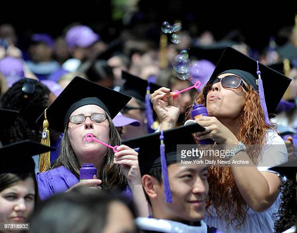 Graduates blow bubbles at New York University commencement ceremony Wednesday at Yankee Stadium