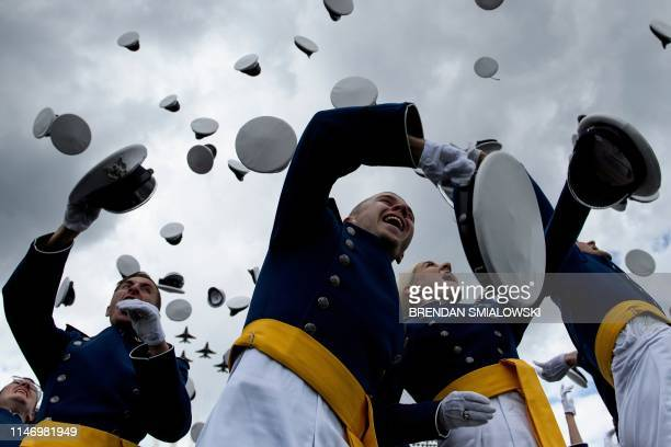 Graduates celebrate and throw up their caps as the Air Force Thunderbirds fly overhead during the 2019 graduation ceremony at the United States Air...