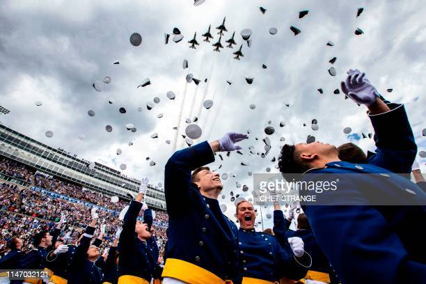 TOPSHOT Graduates celebrate and throw up their caps as the Air Force Thunderbirds fly overhead during the 2019 graduation ceremony at the United...