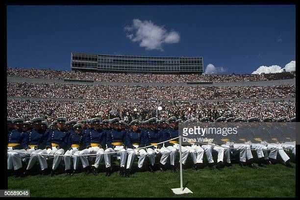 Graduates en masse poised in front of spectatorfilled stands at Falcon Stadium during Air Force Academy commemcement