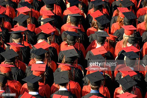 graduates in red and black caps and gowns - headwear stock pictures, royalty-free photos & images