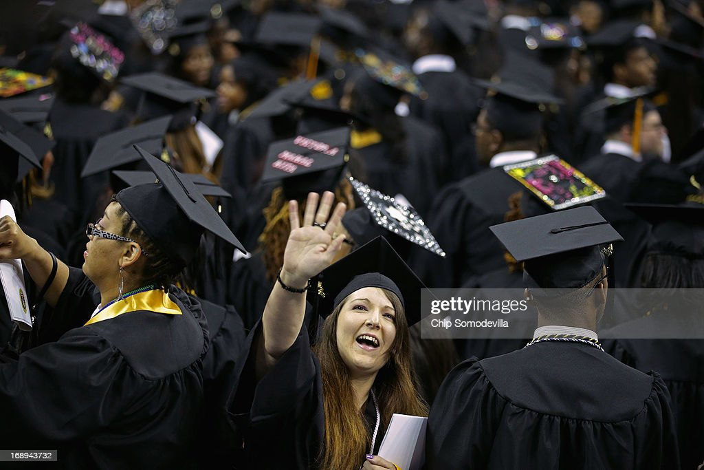 Graduates of Bowie State University wave to friends and family after arriving for the school's graduation ceremony at the Comcast Center on the campus of the University of Maryland May 17, 2013 in College Park, Maryland. First lady Michelle Obama delivered the commencement speech for the 600 graduates of Maryland's oldest historically black university and one of the ten oldest in the country.