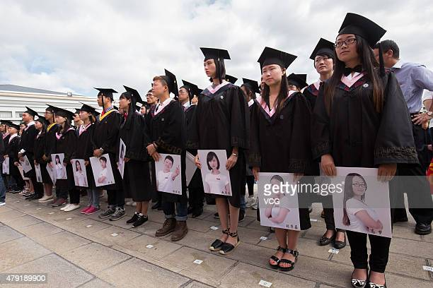 Graduates of Kunming University prepare to put their head portraits on a display board for 'sale' during their graduation ceremony on July 2 2015 in...