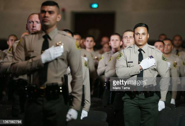 Graduates of Los Angeles County Sheriff's Department Academy Class 451 stand for the pledge of allegiance at their graduation ceremony at East Los...