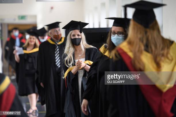 Graduates queue on campus at the University of Bolton as they wait to receive their degree certificates in a Covid-safe, in-person graduation...
