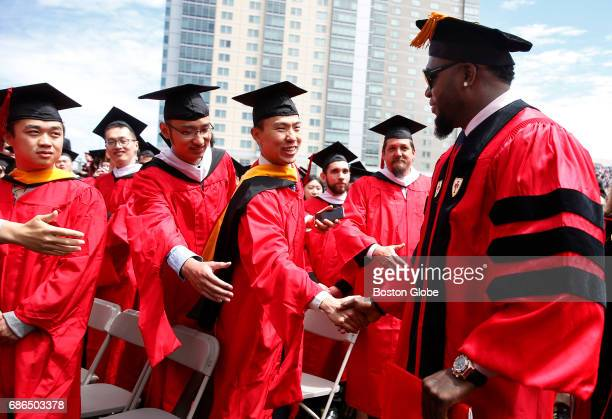 Graduates reached out to shake hands with former Boston Red Sox player David Ortiz during Boston University Commencement on Nickerson Field on campus...