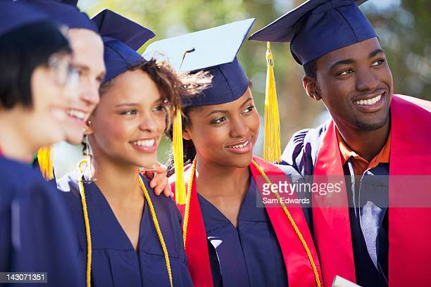 Graduates smiling together in cap and gown