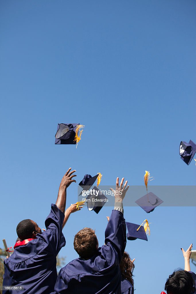Graduates throwing caps in air outdoors : Stock Photo