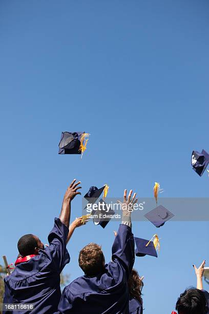 graduates throwing caps in air outdoors - graduation clothing stock pictures, royalty-free photos & images