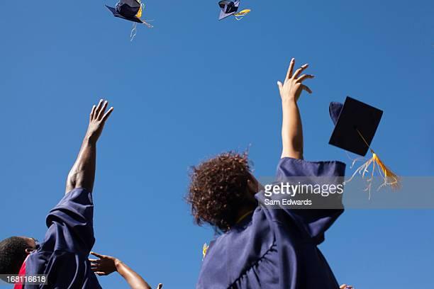 Graduates throwing caps in air outdoors