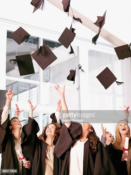 Graduates throwing mortarboards in air