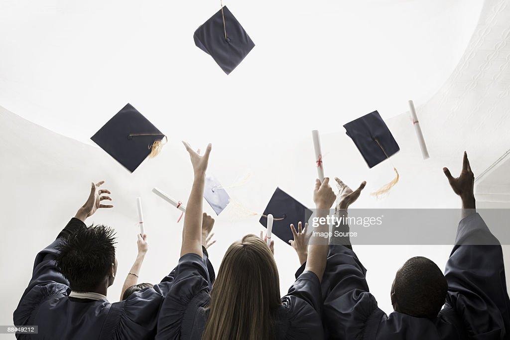 Graduates throwing mortarboards : Stock Photo