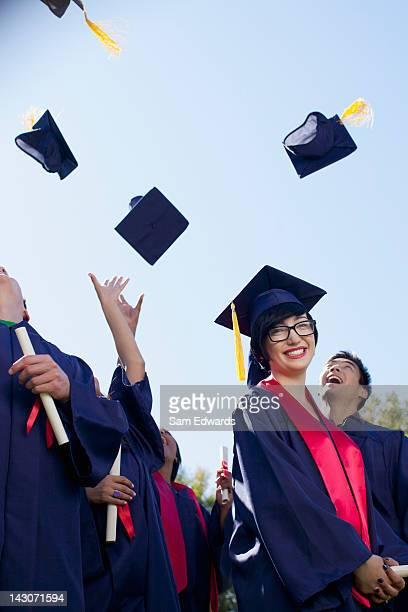Graduates tossing caps in air outdoors