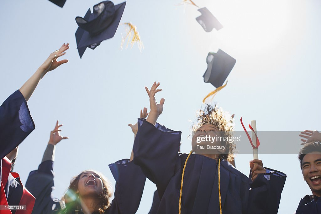 Graduates tossing caps into the air : Stock Photo