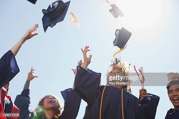 graduates tossing caps into the air - graduation clothing stock pictures, royalty-free photos & images
