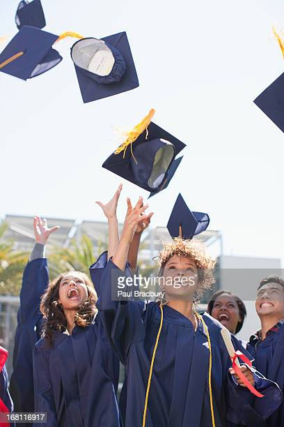 graduates tossing caps into the air - graduation cap stock pictures, royalty-free photos & images