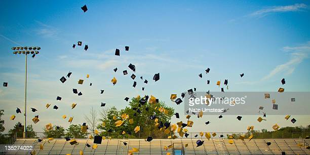 graduates tossing mortar boards in air - graduation cap stock pictures, royalty-free photos & images