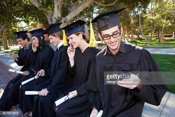 Graduates Using Cell Phones