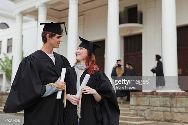 graduates with their degrees on campus - vriendje stockfoto's en -beelden