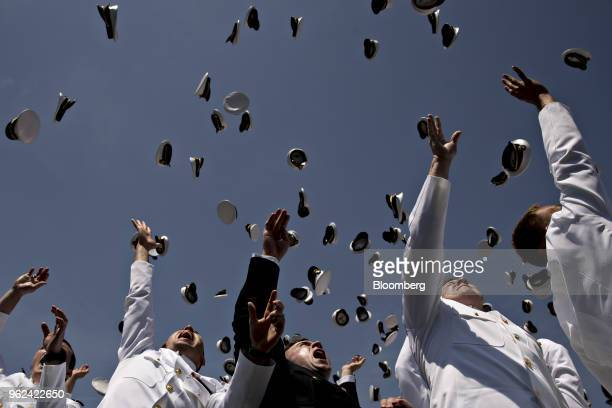 Graduating midshipmen throw their caps in the air during the United States Naval Academy graduation and commissioning ceremony at the NavyMarine...