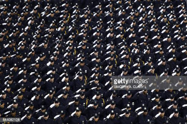 TOPSHOT Graduating officers with the New York Police Department 2016 graduation class salute during a ceremony at Madison Square Garden July 2016 /...