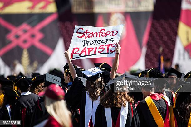Graduating student Andrea Lorei who help organize campus demonstrations holds a sign in protest during the 'Wacky Walk' before the 125th Stanford...
