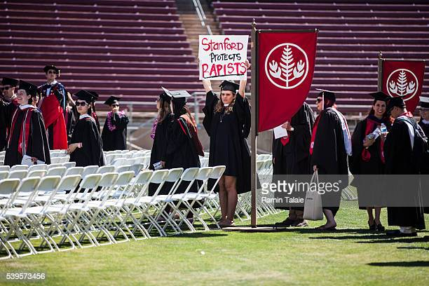 Graduating student, Andrea Lorei, who help organize campus demonstrations holds a sign in protest during the 'Wacky Walk' before the 125th Stanford...