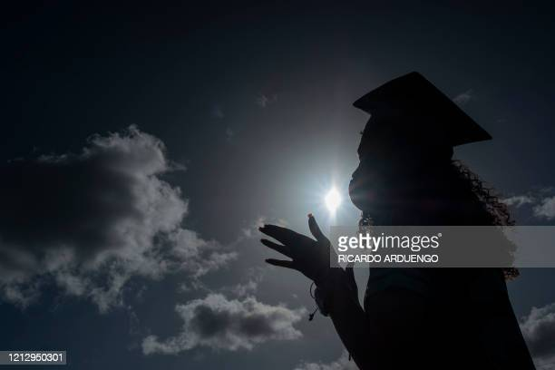 A graduating student from the Ramon Power Y Giralt High School wears a facemask during a symbolic graduation in cars to maintain social distance at a...