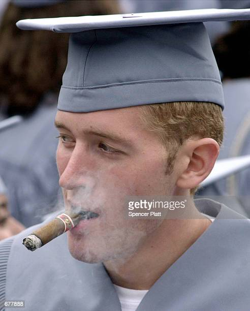 A graduating student smokes a cigar after the commencement address May16 2001 at Columbia University in New York City Columbia one of the oldest...