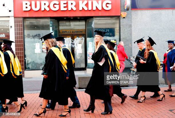 Graduating students walk past a closed Burger King restaurant during a celebratory parade in Walsall town centre on November 29 2019