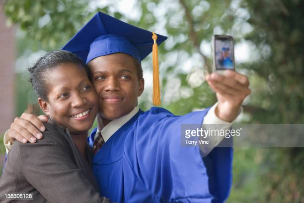 Graduating teenager taking self-portrait with mother