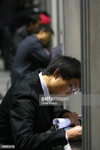 A graduating university student fills in an application form at a job fair on November 28 2008 in Chongqing China The number of Chinese college...