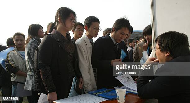 A graduating university student hands in his resume to an employer at a job fair on November 26 2008 in Chengdu of Sichcuan Province China The number...
