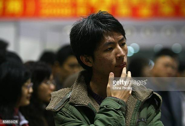 A graduating university student reads employment information at a job fair on November 28 2008 in Chongqing China The number of Chinese college...