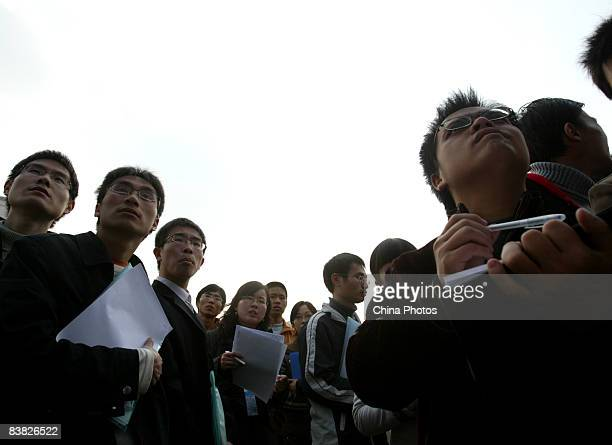 Graduating university students view a company recruitment advertisement at a job fair on November 26 2008 in Chengdu of Sichcuan Province China The...