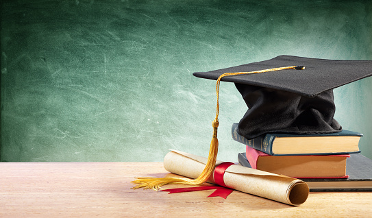 Graduation Cap And Diploma On Table With Books 1154631974