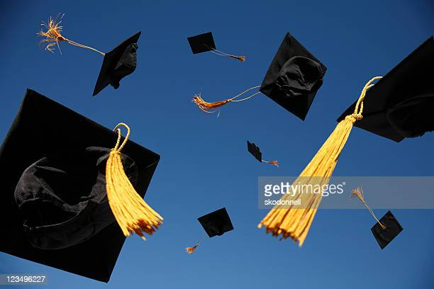graduation caps thrown in the air - graduation stock pictures, royalty-free photos & images