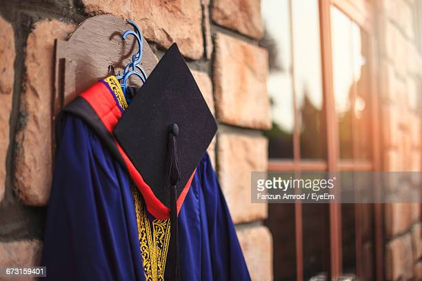 graduation gown with mortarboard hanging on wall - graduation clothing stock pictures, royalty-free photos & images