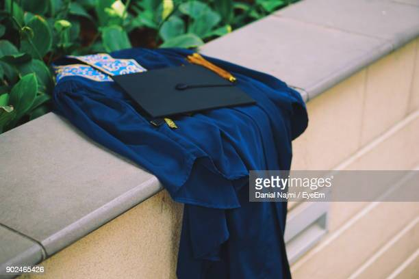 graduation gown with mortarboard on retaining wall - graduation clothing stock pictures, royalty-free photos & images