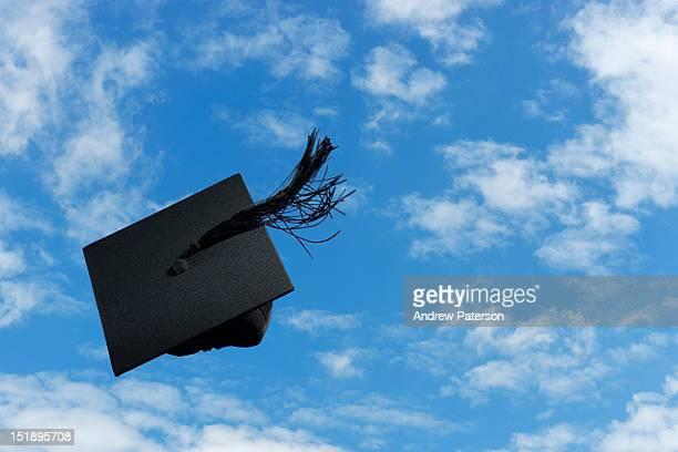 Graduation mortar board thrown in the air