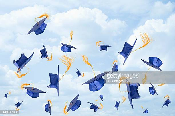 graduation mortarboards being thrown in the air - graduation cap stock pictures, royalty-free photos & images