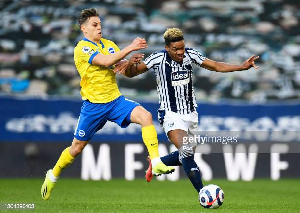 Grady Diangana of West Bromwich Albion is challenged by Leandro Trossard of Brighton and Hove Albion during the Premier League match between West...