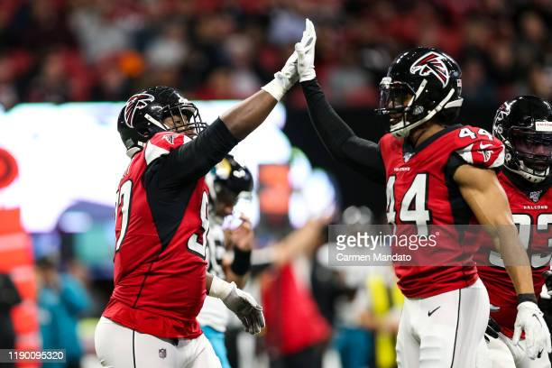 Grady Jarrett of the Atlanta Falcons high fives Vic Beasley Jr. #44 of the Atlanta Falcons during the first half of a game against the Jacksonville...