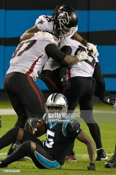 Grady Jarrett, Steven Means and Deion Jones of the Atlanta Falcons celebrates sacking Teddy Bridgewater of the Carolina Panthers during the fourth...