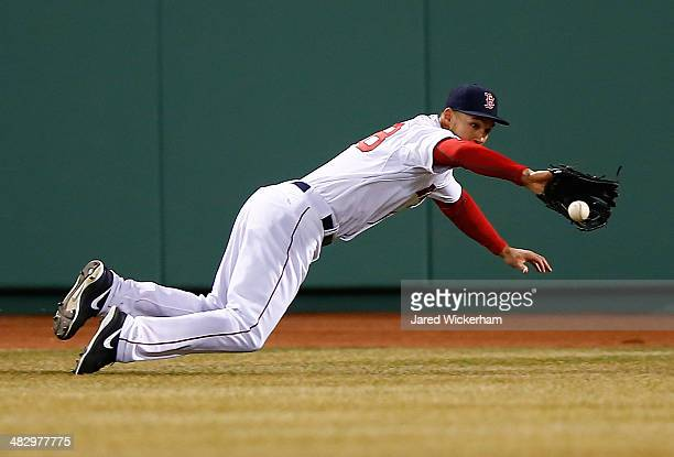 Grady Sizemore of the Boston Red Sox dives for a ball in the outfield against the Milwaukee Brewers durng the game at Fenway Park on April 5 2014 in...
