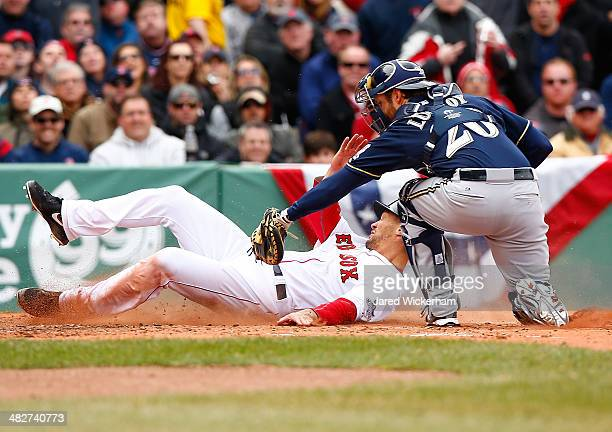 Grady Sizemore of the Boston Red Sox is tagged out at home plate by Jonathan Lucroy of the Milwaukee Brewers in the second inning during the Opening...