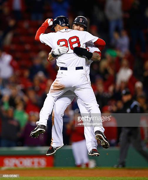 Grady Sizemore of the Boston Red Sox jumps into the arms of teammate Mike Napoli after hitting his walkoff hit in the bottom of the 12th inning...